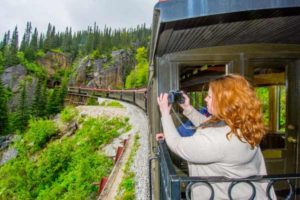 Tourist rides train in Skagway and shoots photos of scenery