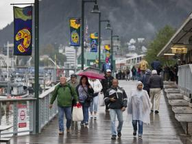 Michael Penn, Juneau Empire Cruise ship passengers walk in the rain back to their ship in early September.
