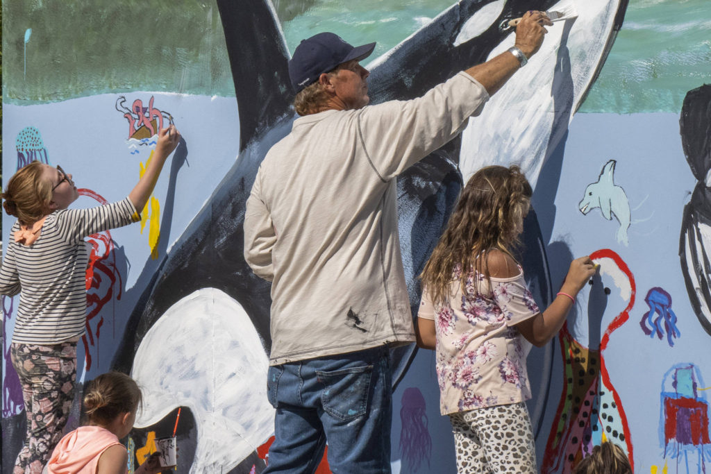 Wyland, a Laguna Beach-based artist, paints a mural with Southeast Alaska children